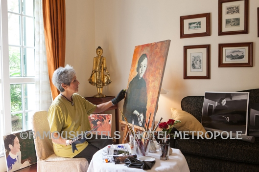 Joan Baez entering a new career: she is painting a portrait at her suite at the Hotel Metropole. Later, she donated that painting to the hotel.